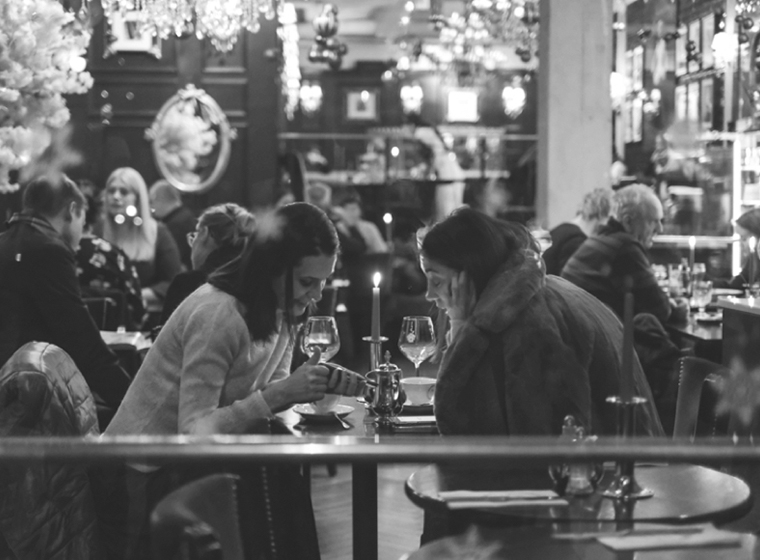 Two ladies sitting in a restaurant talking.