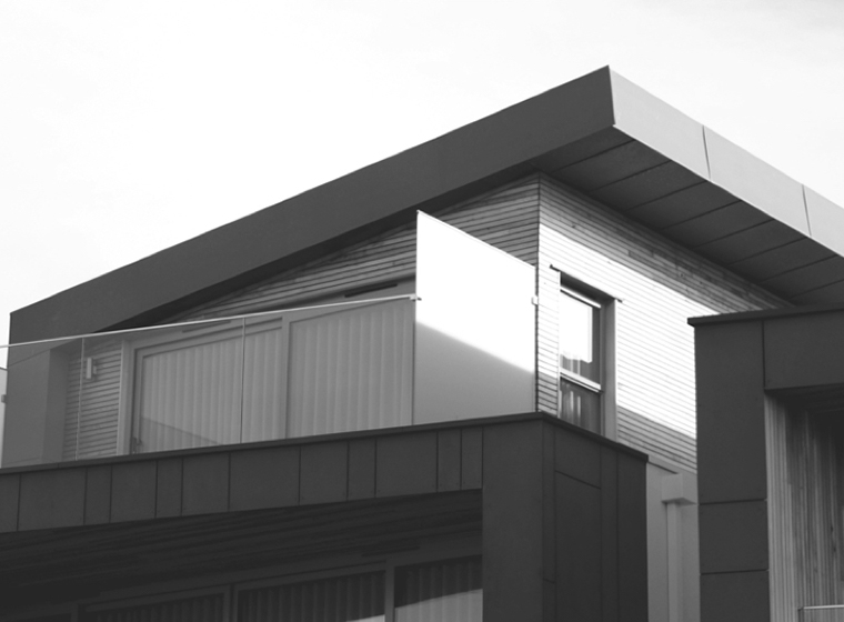 A building exterior showing a deck and the top portion of the building.