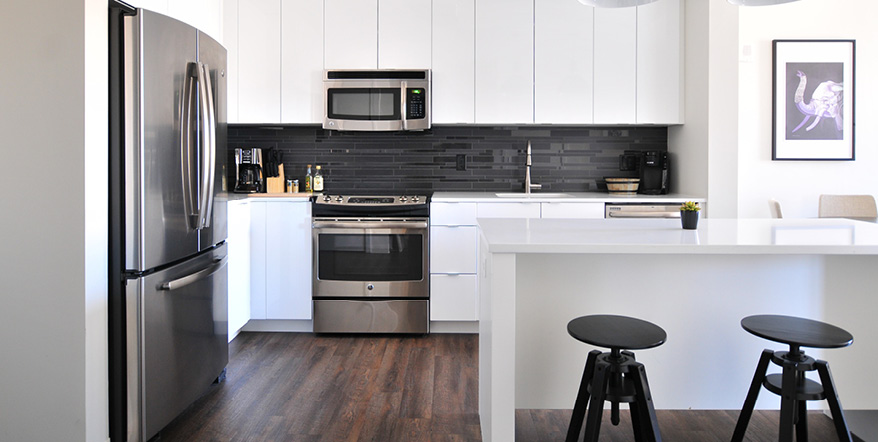 Image of newly renovated kitchen with hardwood floors and new cabinet.
