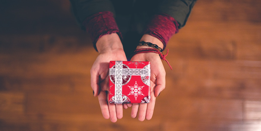 Image of two open hands offering a small, wrapped gift.