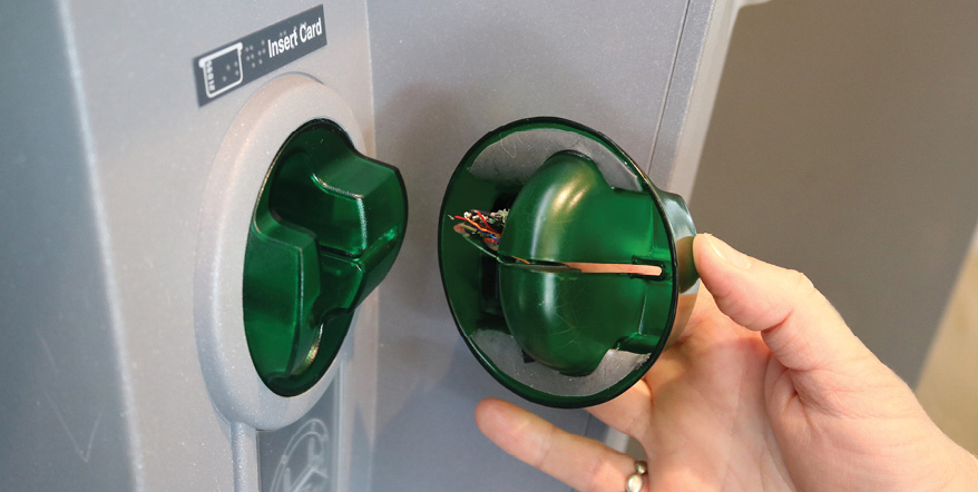 Image of a person using a mirror to spot a card skimmer in an ATM
