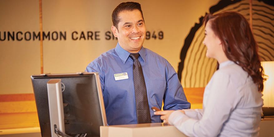 Image of smiling NWCU employee helping a member.