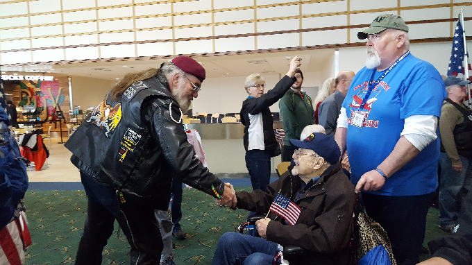 Image of Rocky and a few veterans in the airport.