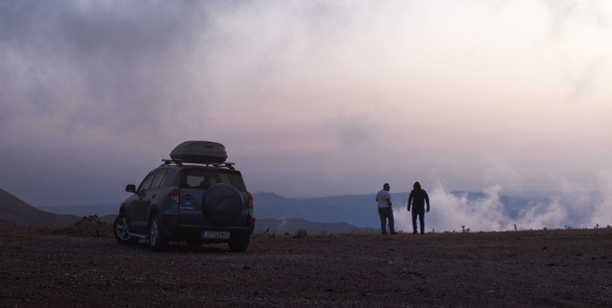 Image of two people overlooking a cliff next to their parked car.