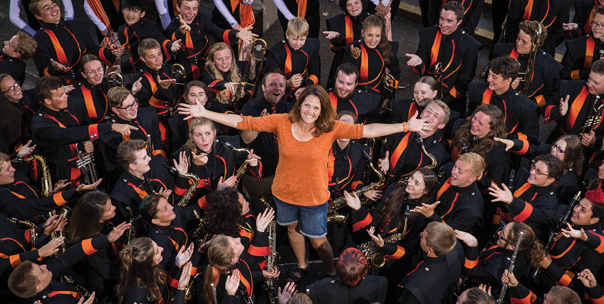 Image of Lori Adams standing in the middle of several Roseburg High School band students.