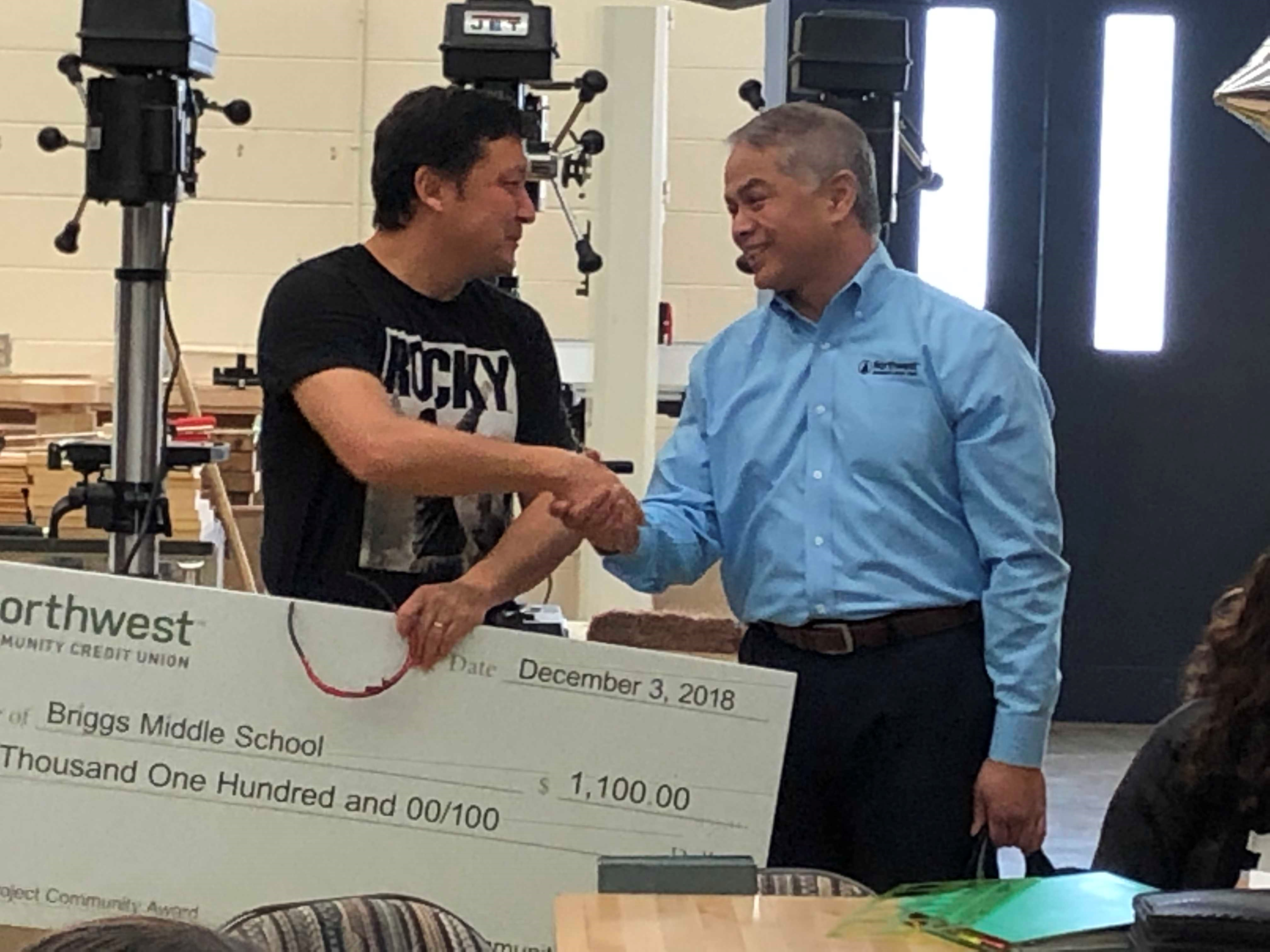 NWCU CEO John D. Iglesias shaking hands and presenting an oversize check to Joe Hass in his classroom
