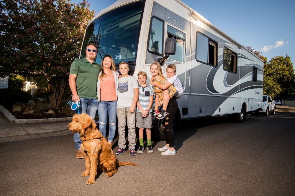 Adam and Mitzi Coleman with their four kids and family dog in front of their RV