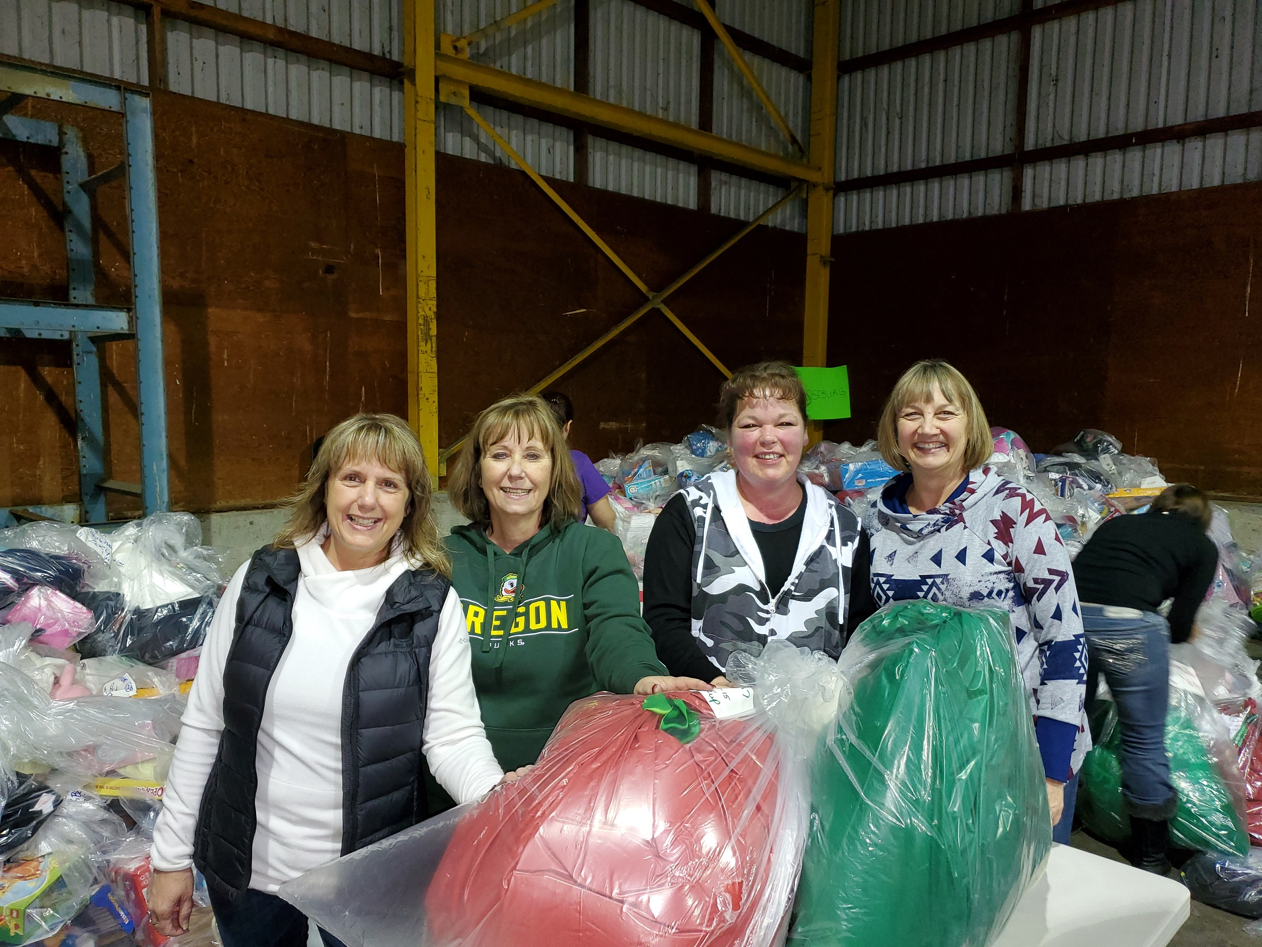 Roseburg branch managers and staff bag gifts for Christmas for Kids of Douglas County